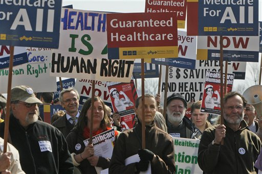 Protestors hold signs at a rally  in Burlington, Vt., Tuesday, March 17, 2009. Advocates of a single-payer health care system rallyed outside a Burlington building where a White House-organized forum is scheduled. About 125 people waving signs and chanting have gathered outside the Davis Center of the University of Vermont campus to promote their cause.(AP Photo/Toby Talbot)