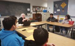 Ms. Lane holding a seminar with freshmen gifted students gathered around a round tables.