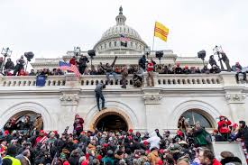 Rioters as they climb the walls of the capitol building.